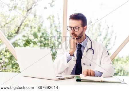 Careworn Male Doctor Working On Laptop And Desk In The Hospital