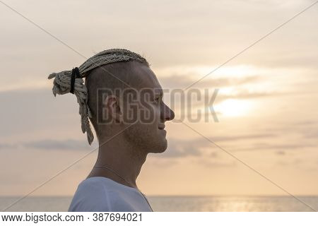 Silhouette Of A Young Guy With Dreadlocks On His Head Near Sea During Sunset. Close Up Portrait. Hap