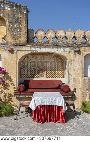 Street Cafe In Old Town, Outside In Jaipur, Rajasthan, India. Table, Sofa And Chairs Near Old Wall