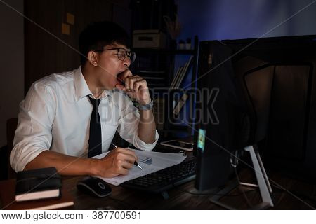 Businessman Workaholic Sit At The Computer Working Late At Night Yawn Tired And Sleeping In The Offi