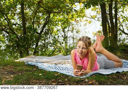 A Young Girl Lies On A Rug In The Park. Autumn Picnic. Young Girl Lying On A Blanket In The Autumn F