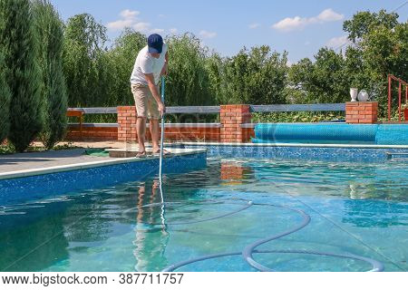 Cleaner Of Swimming Pool. Man Cleaning Outdoor Swimming Pool With Vacuum Tube Cleaner In Summer. Sea