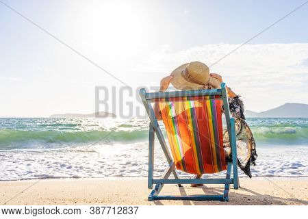 Woman sitting on a deck chair at the tropical beach