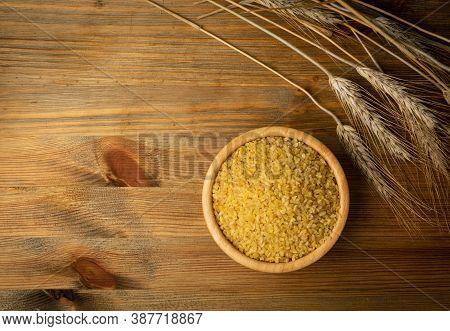 Bulgur, Bulgour Or Bulghur In Wooden Bowl On Wood Background