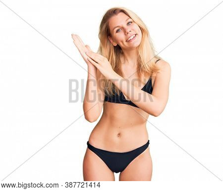 Young beautiful blonde woman wearing bikini clapping and applauding happy and joyful, smiling proud hands together