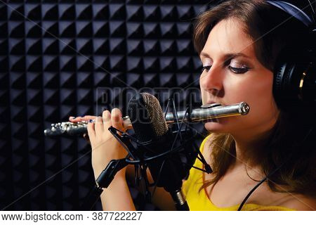Girl Flute Player Plays In Music Studio, Copy Space. Record Wind Musical Instruments With A Professi