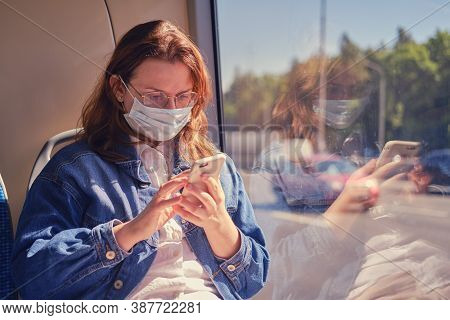 A Woman In A Medical Mask Looks At The Bus Route On Her Phone. A Tourist Looks At The Details Of The