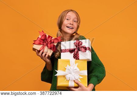 Image Of Charming Blonde Girl 12-14 Years Old In Warm Green Sweater Holding A Lot Of Gift Boxes. Stu