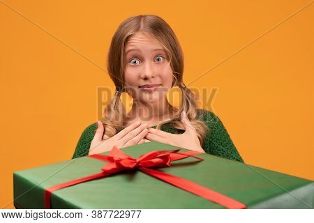 Charming Blonde Girl 12-14 Years Old In Warm Green Sweater Take A Gift From A Friend With Red Ribbon