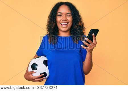 Young african american woman holding football ball looking at smartphone winking looking at the camera with sexy expression, cheerful and happy face.