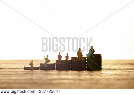 Silhouetted Figures Backlit By A Bright Glow And Copyspace, Sitting On Stacks Of Money In Ascending