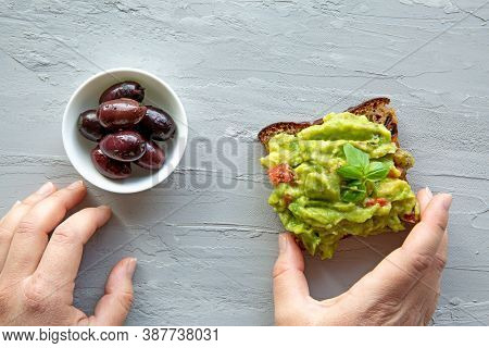 Female Hands Hold Tasty Avocado Toast, Close Up. Top View.