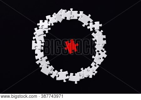 Red Piece Located Separately In Center. White Puzzles Are Scattered Around In Circle On Background.