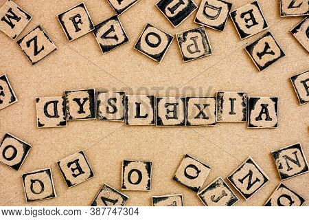 Word Dyslexia Spelled Out From Cardboard Letters Made By Black Alphabet Stamps.