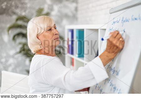 Concentrated Senior Female Teacher Writes Algebra Formulas On A Whiteboard In Modern Classroom