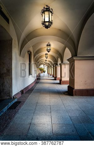 Arcades Or Archway With Long Corridor Illuminated By Vintage Lanterns. Townhall Building On City Squ