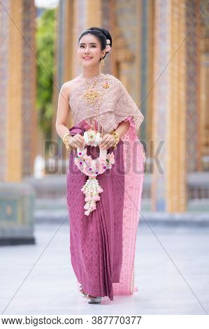 A Beautiful Elegant Thai Woman In Thai Dress Adorned With Precious Jewelry Stands Holding A Flower G