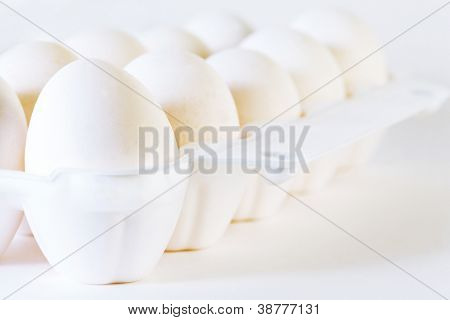 Close up of ten white eggs in white container on white background.