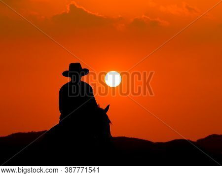 The Western Cowboy Forced His Horses To Stop While The Sun Was Setting, In Lands Where The Law Has N
