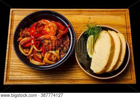 Close-up Of Seafood Salad With Prawns, Calamari (squid), Mussels And Pepper In A Bowl And Bread With
