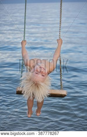 Happy Blond Boy Rides Rope Swing Over The Water On Sea Background. Vertical Frame.
