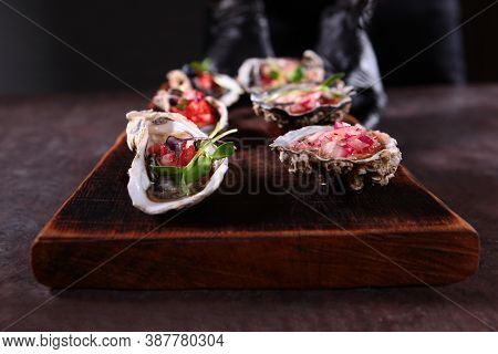 Two Types Of Oysters With Savory Sauces On A Wooden Board. Oyster Season. Unrecognizable Photo.