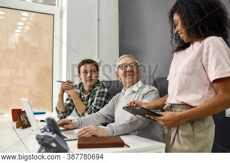 Aged Man, Senior Intern Smiling To His Young Colleague While Using Laptop, Friendly Workers Mentorin
