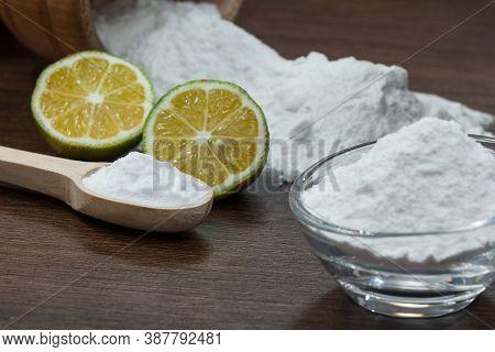 Baking Soda - Sodium Bicarbonate And Lemon; On Dark Wooden Background.