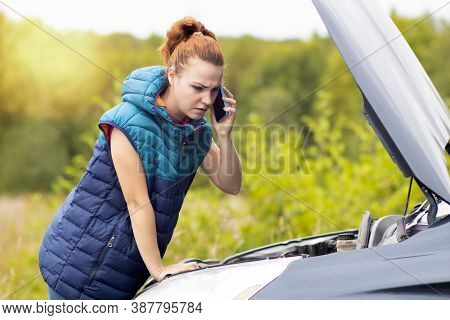 Sad Woman Looks Under The Hood Of Her Car On The Side Of The Road, Talking On The Phone. Traffic Acc