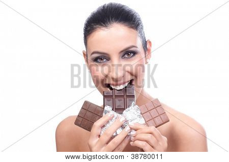 Attractive young woman holding several chocolate bars, biting one, smiling.