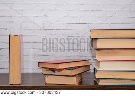 A Few Books Of Various Sizes Arranged On A Dark Wooden Shelf, With A White Painted Brick Wall In The