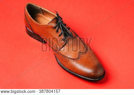 Mens Shoes. Brown Leather Shoes Isolated On A Red Background. Boots Made Of Genuine Leather Close-up