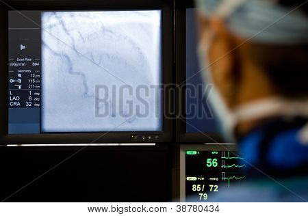 Doctor with mask observing medical procedure on the monitor, focus on screen