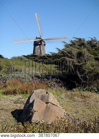 Large Rock In Field And Golden Gate Park North Dutch Windmill In San Francisco.