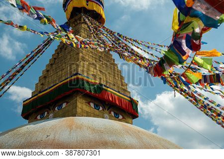 Multicolored Buddhist Prayer Flags With Mantras On A Background Of Blue Sky And An Ancient Stupa. Tr