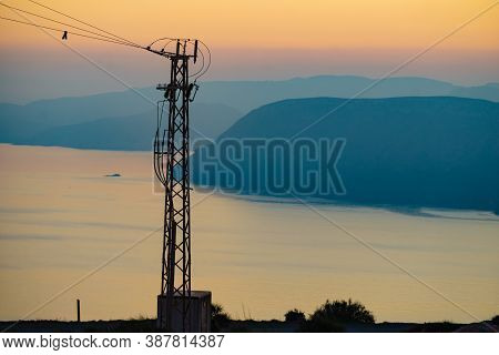 Coast With Electricity Transmission Pylons, Power Lines High Voltage Towers. Sunset Landscape In Spa