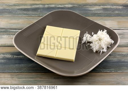 White chocolate candy bar with coconut bits and shredded sweet coconut on candy dish