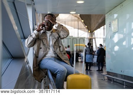 Stressed Black Man In Spectacles Shocked With Bad News, Talking On Mobile Phone, Sitting In Airport,