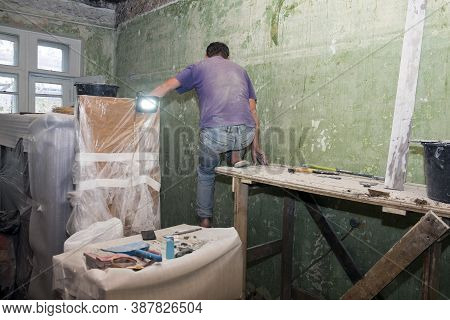 Plaster Works In A Room With A Worker Sitting On The  Trestles, Indoor Shot