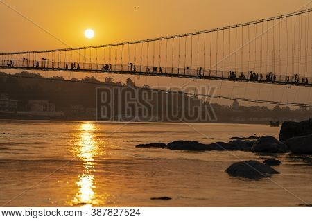 Beautiful View Of Ganges River Embankment And Bridge At Sunset. Rishikesh, India