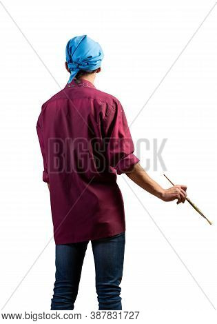 Young Male Painter Artist Holding Paintbrush. Back View Of Painter In Shirt And Bandana Standing On