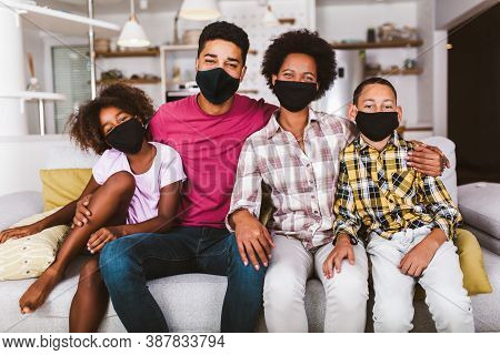 African American Parents And Cute Small Kids Wearing Protective Masks At Home. Stop The Virus And Ep