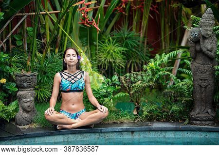 Yoga. A Young Woman In A Bathing Suit, Meditating By The Pool, Closing Her Eyes. In The Background,