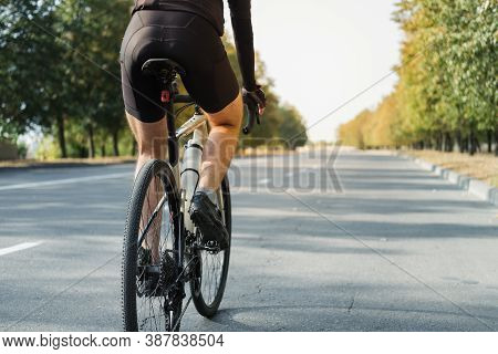 Man On A Gravel Bike On The Road, Back View. Legs Of A Cyclist Riding A Modern Bicycle Outdoors