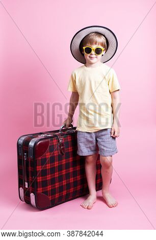Travel: A Little Boy In A Straw Hat And Sunglasses Plays A Tourist And Sits On A Big Red Suitcase.