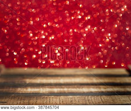 Wooden Table With Selective Focus On Red Abstract Background With Defocus Lights. Christmas Xmas Or