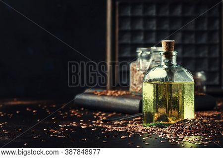 Linseed Or Flax Oil In Glass Bottle And Seeds, Dark Background, Selective Focus