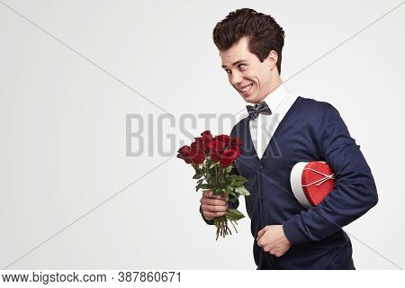 Eccentric Young Male With Bouquet Of Roses And Gift Smiling And Looking At Empty Space During Date O