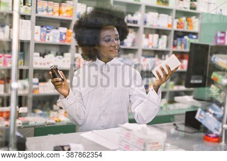Medicine, Pharmacy, Healthcare Concept. Happy Female African Apothecary Worker Posing At Pharmacy Ho