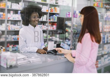 Pretty Young Caucasian Woman Paying For Mediciens With Credit Card In Pharmacy. Smiling Attractive A